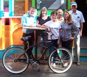 Committee members for the 10th Annual Stuff-A-Bus Harborfest Breakfast display the Beach Cruiser bicycle donated by Dan Dorsey of Eagle Beverage
