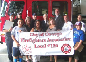 Oswego Mayor Tom Gillen joins members of the City of Oswego Firefighters Association Local 126 in presenting a donation of school supplies to the United Way's Stuff-A-Bus campaign