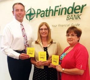 Patrick Dewine joins Pathfinder Bank employees Melissa Miller (c) and Carol Shannon (r) in displaying United Way's Paper Buses